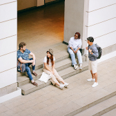 Four international student sitting and standing in the entrance area of a university building.